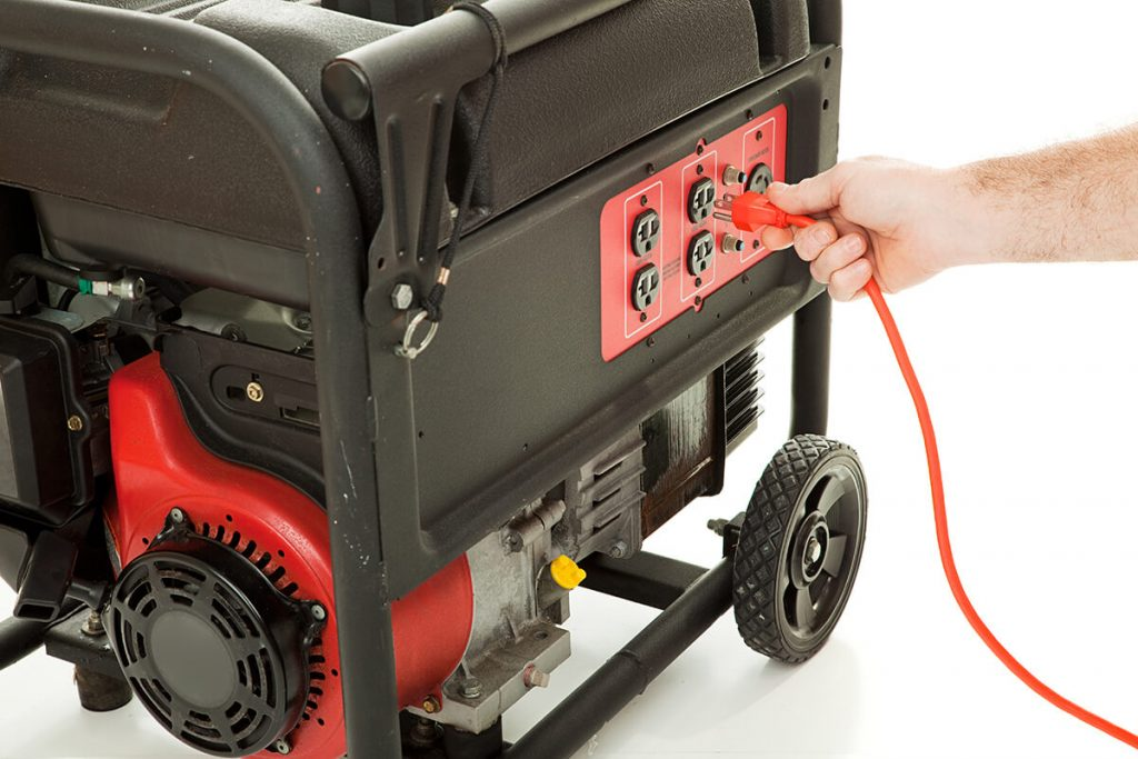 Generator Installations - Hand plugging a cord into a generator