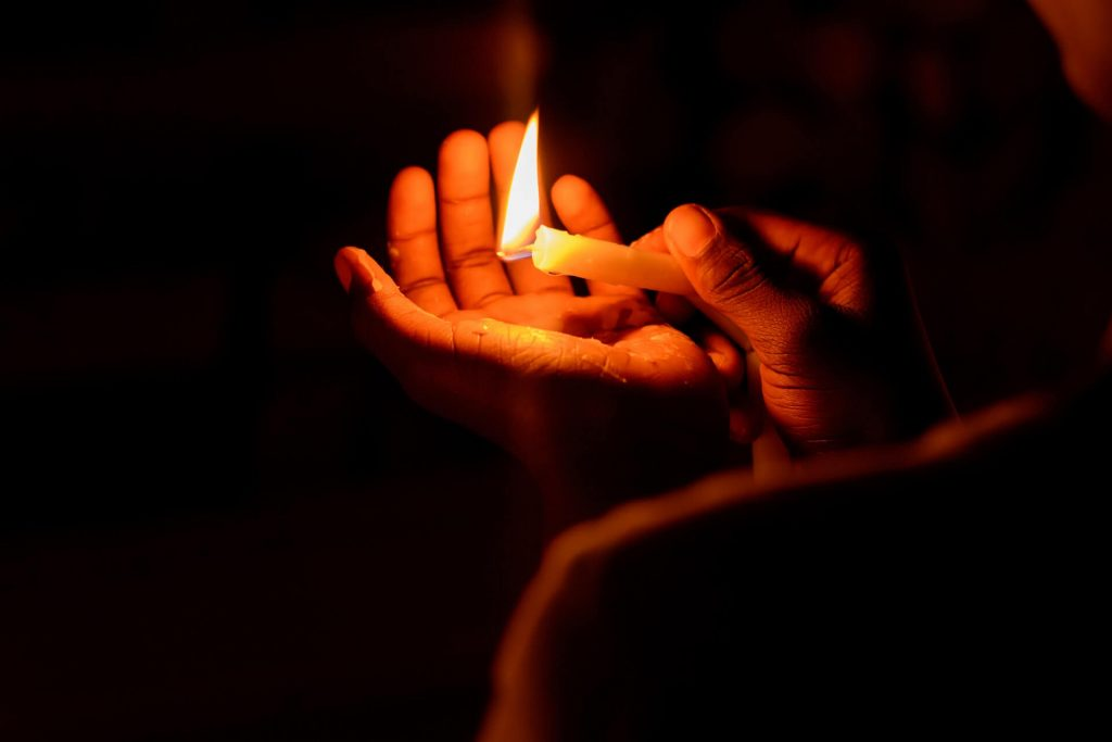 Power Outages Oregon - hands holding lit candle in power outage